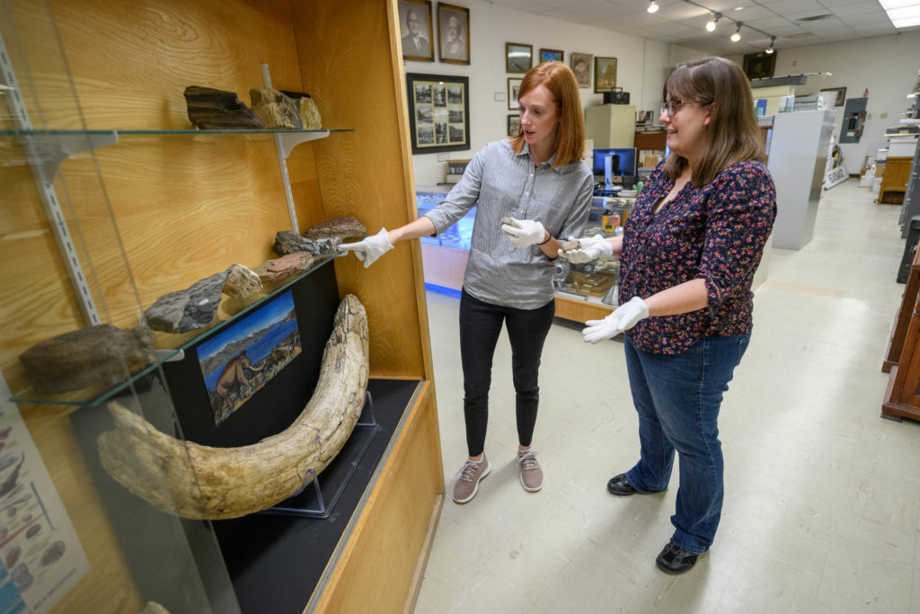 Image of LADWP representative and museum curator examine the specimens in the museum's Fossil Case, which include the proboscidean tusk and artwork