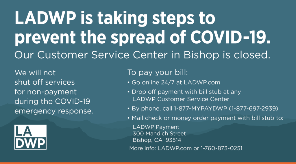 message on COVID-19 customer service centers in Bishop are closed with mountains in background.