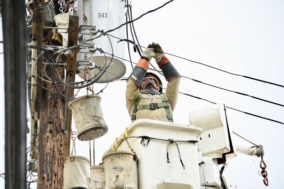 Image of lineworker repairing power line.