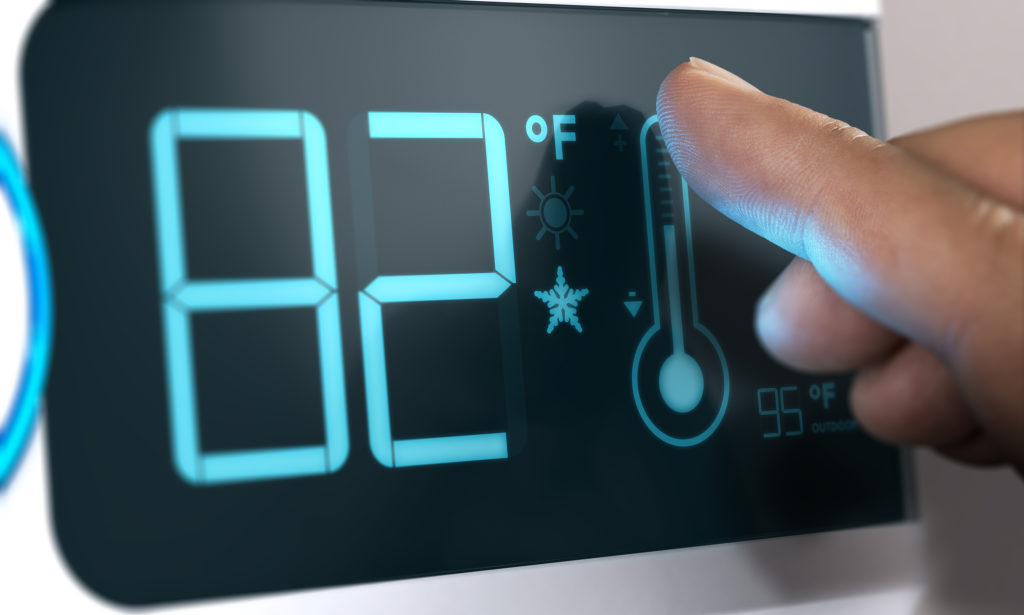 Finger touching a digital thermostat temperature controller to set it at 82 degrees fahrenheit. Composite between an image and a 3D background