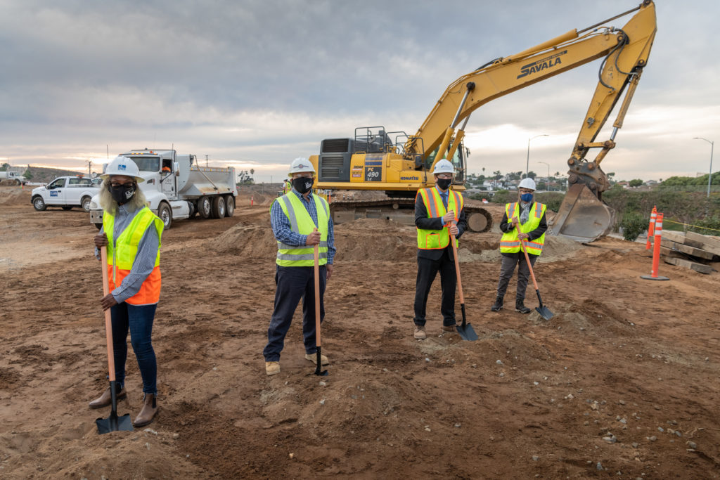 4 people socially distanced at construction site with shovels