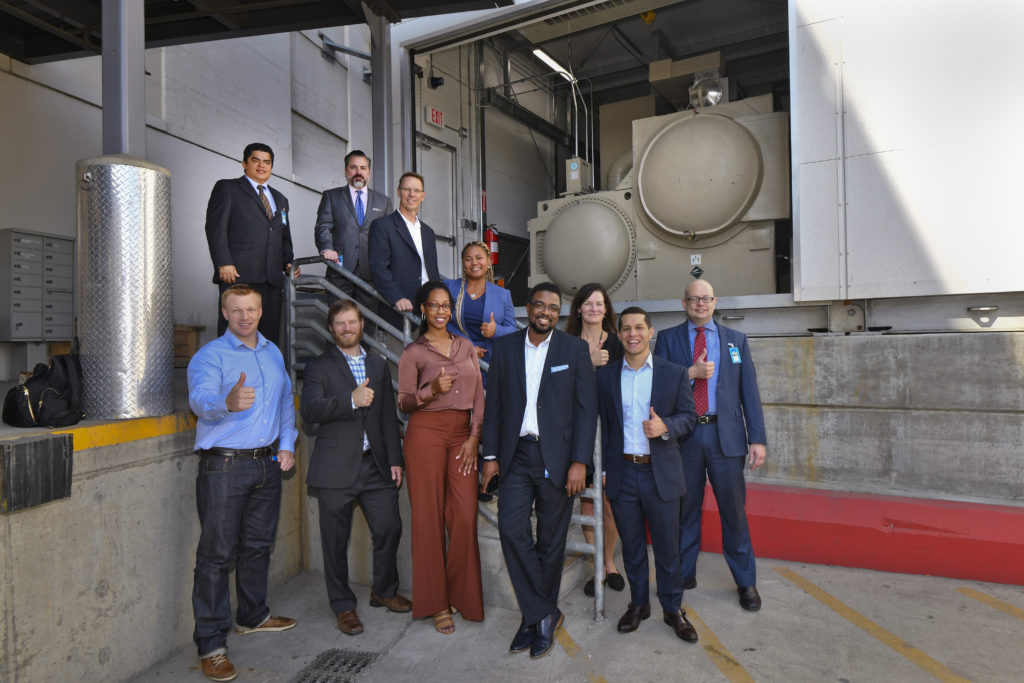 Three women and 8 men in office attire standing on an exterior staircase giving thumbs up in front of HVAC cooling machinery