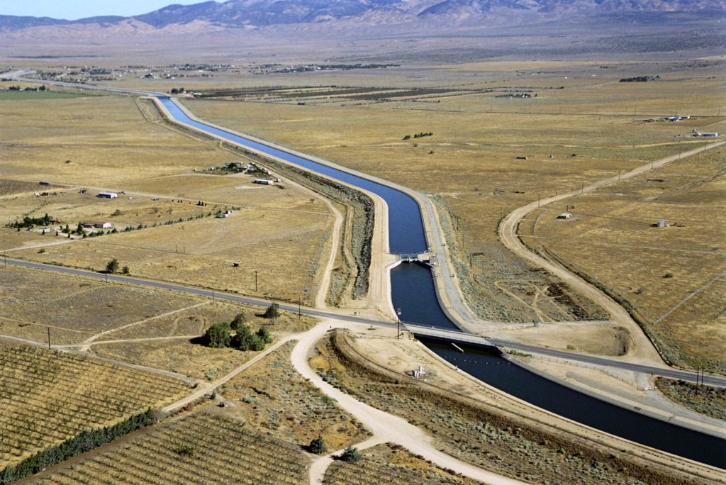 Water in aqueduct making its way across desert with mountains in the background