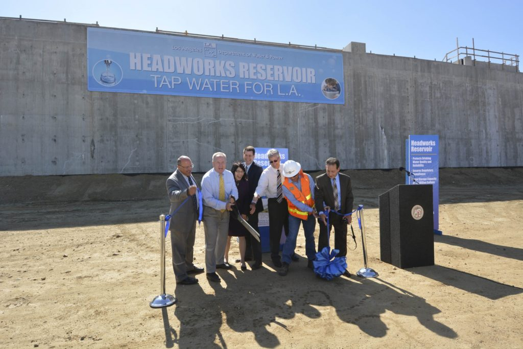 Image of a group of people next to a podium and in front of a large structure with sign that reads headworks reservoir