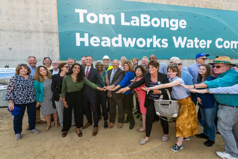 Image of a group of people in front of a large banner that reads tom labonge headworks water complex