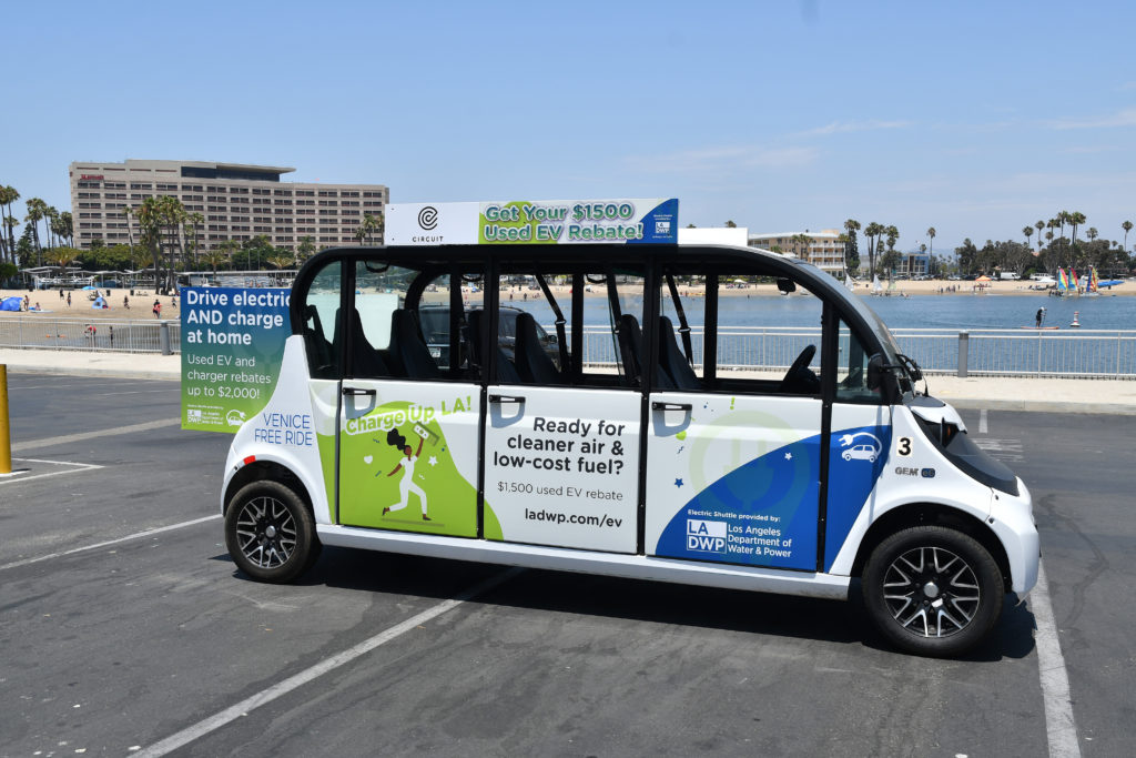 Image of a small electric powered vehicle parked in a beach parking lot with a building in the background