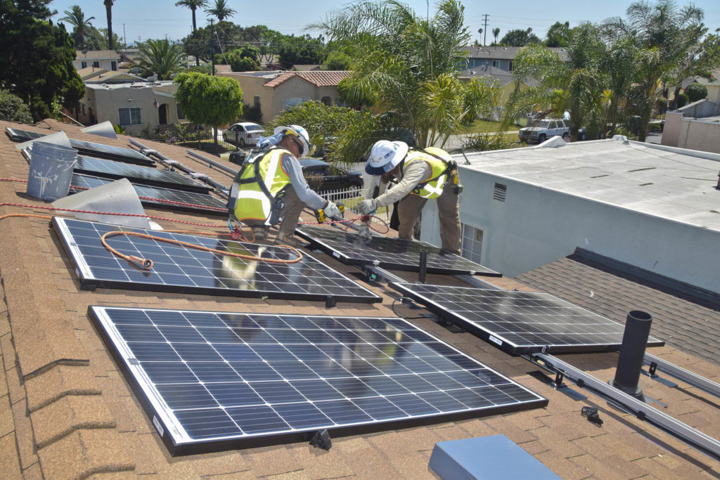 Image of two workers in hard hats and neon safety vests on an LA city rooftop installing solar panels