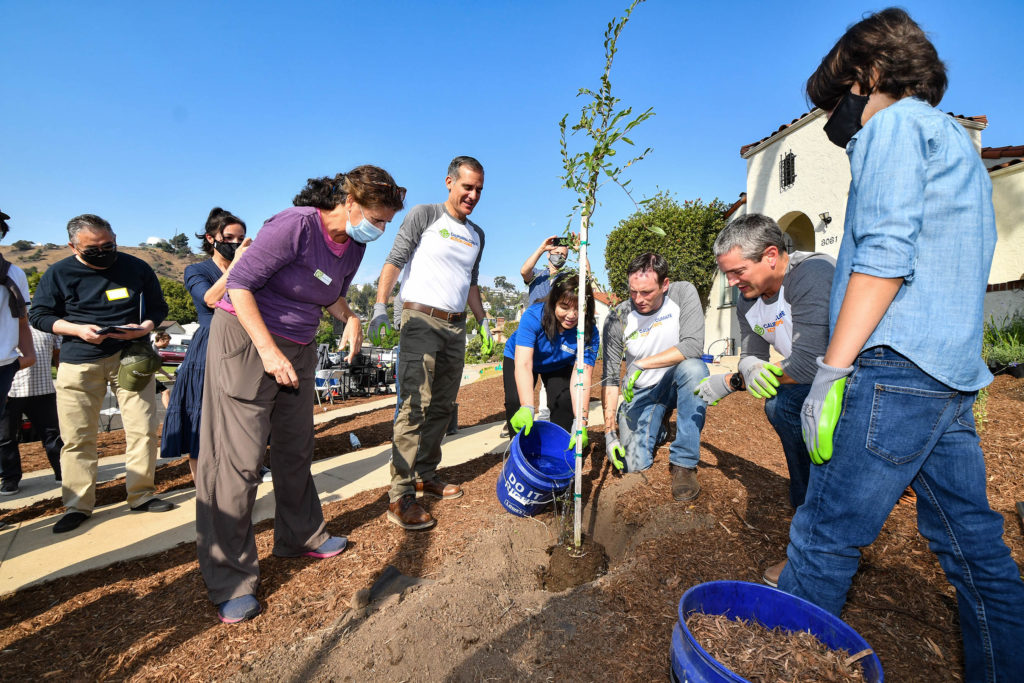 Image of LADWP Commission VP Susana Reyes pouring water in a new tree planting. She is being helped by others including Mayor Eric Garcetti to the left.